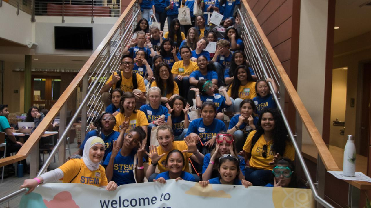 2018 Stem for Girls group sitting on stairs holding Stem for Girls Banner making funny faces.