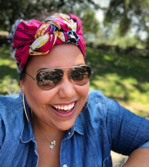 Assistant Director of Outreach Sara laughing. Sara is wearing a pink and yellow patterned head wrap and sunglasses outside.