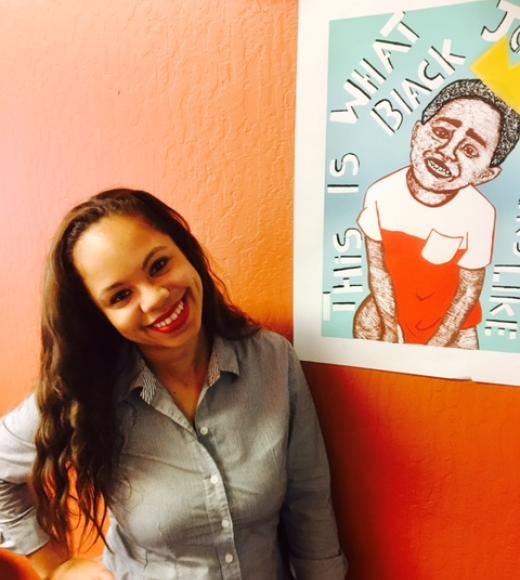 Director Cecily is bending with hand on right hip smiling into the camera with her hair hanging over her shoulder. Black Joy art work is on the left hanging on a rust orange wall.