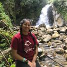 CO Joceline Gonzalez, smiling into camera, hair in braids sitting in font of a waterfall