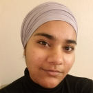 Gursimran smiling at camera wearing head wrap and black shirt.