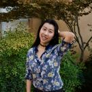 CO Kathy Pham is outside in front of bushes wearing a floral button down shirt tucked into her pants. Kathy is smiling into the camera with her hair down and her arm bent behind her head.