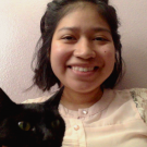 CO Martha Campos smiling at camera wearing a white buttoned shirt in front of a white wall. Black cat is in foreground of photo.